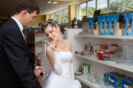 Groom and bride holding soup ladle in kitchen utensils section of a store photo