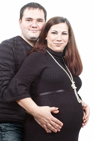 Happy pregnant wife with husband hugging her belly isolated on white photo