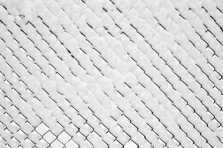 Chain link fence covered under fresh snow   photo