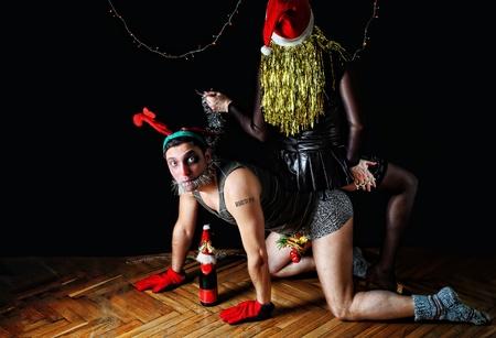 Bad santa femmina seduta sul maschio vestita come Rudolph le renne naso rosso su sfondo scuro Archivio Fotografico