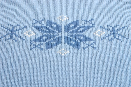 Part of blue woven fabric with knitted snowflakes and selective focus photo
