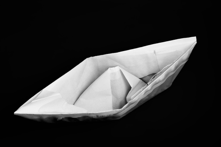 sunk: Closeup of sinking folded paper ship against black background with selective focus