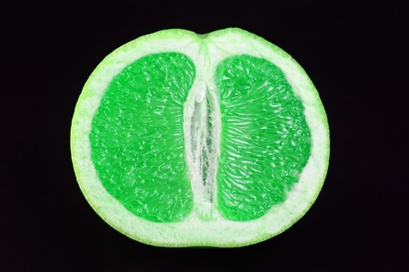 cut half of green juicy grapefruit on black with selective focus Stock Photo - 8864444