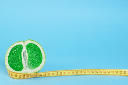 Cut half of green juicy grapefruit with centimeter on blue background with copy space Stock Photo