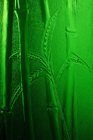 Vertical shot of green embossed bamboo leaves and stems on stained glass photo