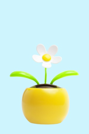 Daisy flower toy with green leaves in yellow flower pot isolated on blue background with copy space Stock Photo - 8867733