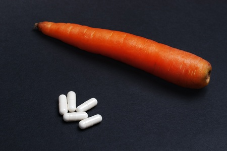 enteric: White enteric coated tablets and a whole raw carrot on black textured background