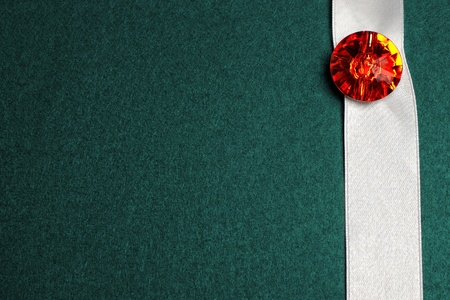 White ribbon with red precious stone on dark cyan textured background with copy space photo