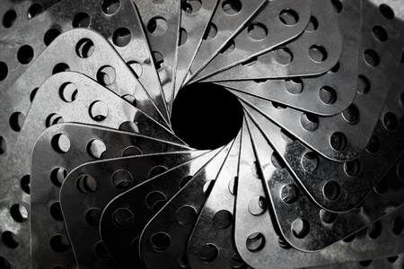 Closeup of rolled industrial steel equipment with a black hole inside and selective focus photo