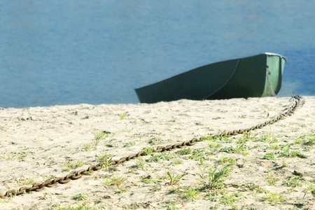 Long rusty chain on sand beach with blurred boat and blue water photo