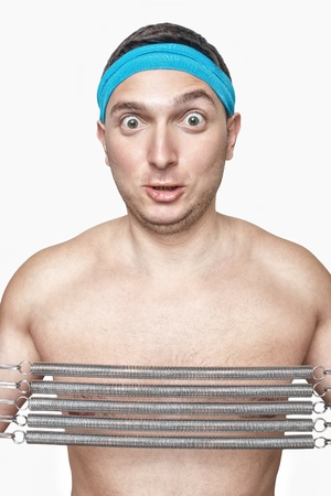 Funny guy with blue sweatband pulling coil springs expander isolated on white