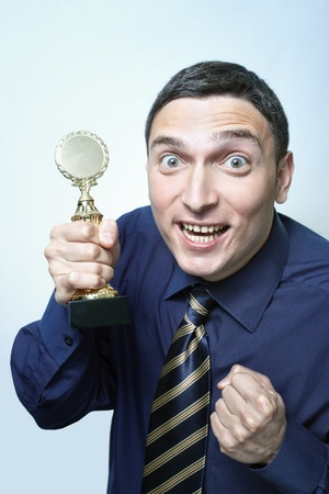 Young man in shirt and tie being crazy happy about winning a golden trophy Stock Photo