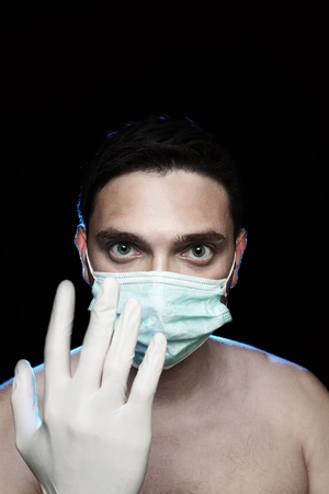 Closeup of scary man in surgical mask and white glove against dark background
