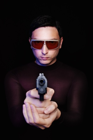 Criminal hitman in sunglasses pointing a gun in the dark with blue light reflection Stock Photo - 9663643