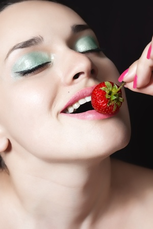 Closeup of beautiful young woman face with pink full lips ready to eat strawberry with selective focus Stock Photo - 9663668