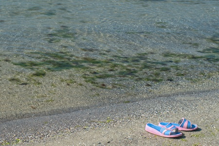 sneaks: A pair of pink slippers on the beach next to the sea with selective focus and copy space