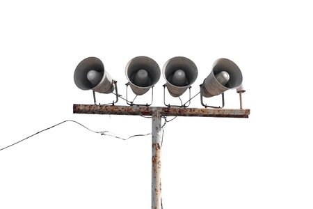 Row of loudspeakers on old rusty pole isolated on white