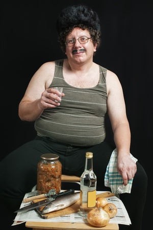 russian hat: Russian man in glasses and fur hat drinking vodka with onion and herring against dark background