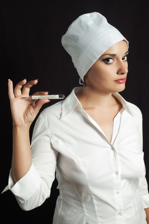 female doctor or nurse in white cap showing glass thermometer against dark background photo