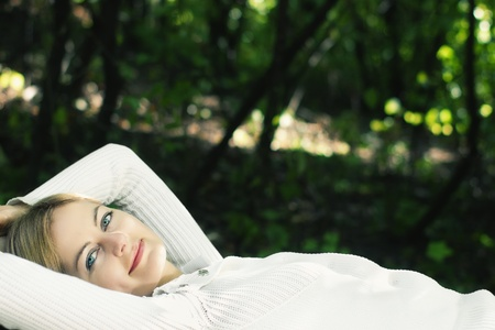 Lying young blue-eyed smiling woman in white against blurred forest background with selective focus and copy space photo