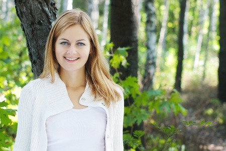 young blue-eyed smiling woman in white against blurred forest background with selective focus and copy space photo