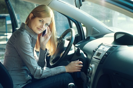 Young blue-eyed businesswoman talking on the cell phone inside her car  Stock Photo - 10931985