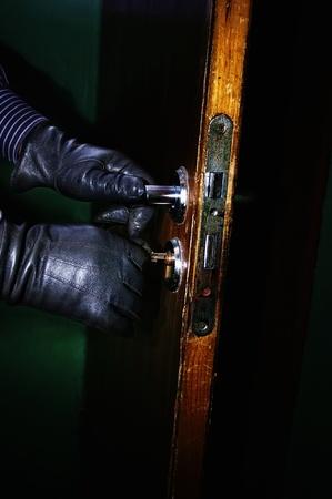 Primo piano di mani ladro in guanti di pelle aprire una porta nella notte, con messa a fuoco selettiva