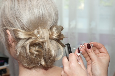 Stylist hands making hairdo with a hairpin