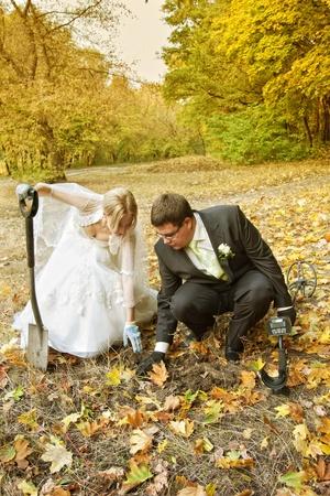 Sposa e sposo in cerca di anelli con metal detector nella foresta