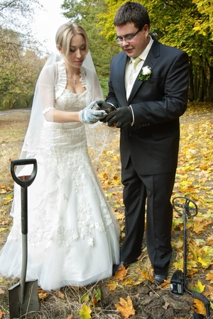 detecting: Bride and groom opening a dug out treasure box found with metal detector in the forest with selective focus Stock Photo