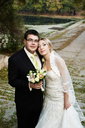 Bride with a tattoo and groom with eyeglasses outdoors in the fall with selective focus photo