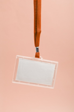 Hanging blank business plastic badge with orange neck strap against rosy background  photo