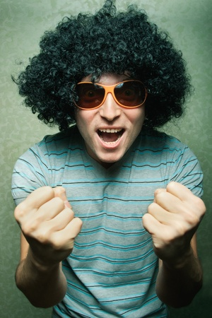 crazy young guy in afro curly wig with eyeglasses photo