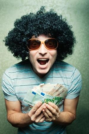 Felice ragazzo in parrucca afro ricci con un sacco di soldi in possesso di occhiali da vista