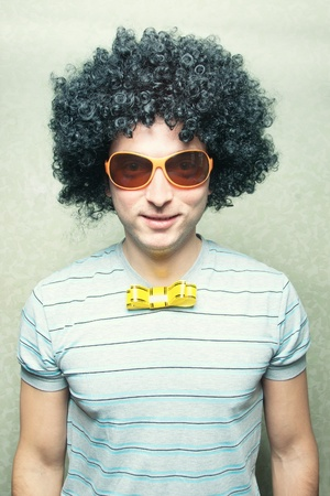 funny smiling guy in afro curly wig with eyeglasses and ribbon bow-tie  photo
