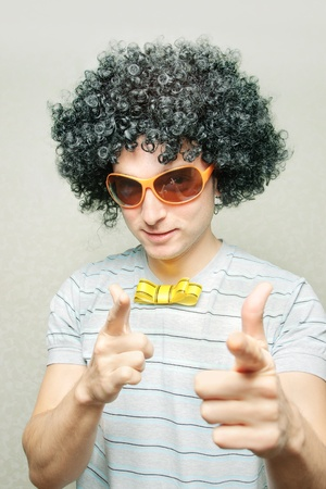 funny guy in afro curly wig with eyeglasses and ribbon bow-tie pointing with his fingers