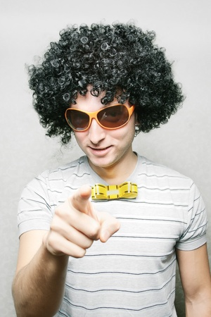 dork: funny guy in afro curly wig with eyeglasses and ribbon bow-tie pointing with his finger Stock Photo