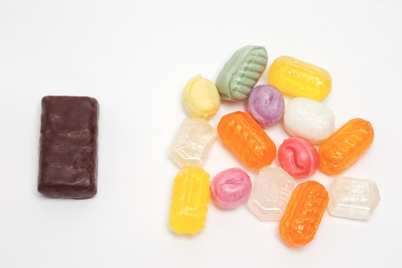 variance: bunch of multicolored sweet caramel candies and chocolate bonbon on white