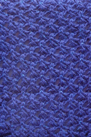 spangles: Vertical closeup of dark blue woolen texture with sparkling tinsel spangles
