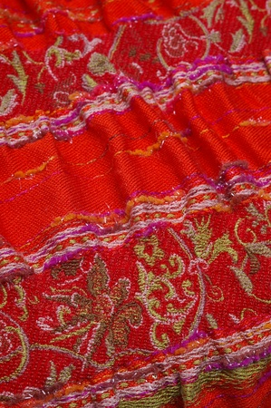 Vertical closeup of red eastern scarf with white interwoven ornament with selective focus photo