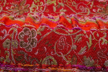 Closeup of red eastern scarf with white interwoven ornament with selective focus photo