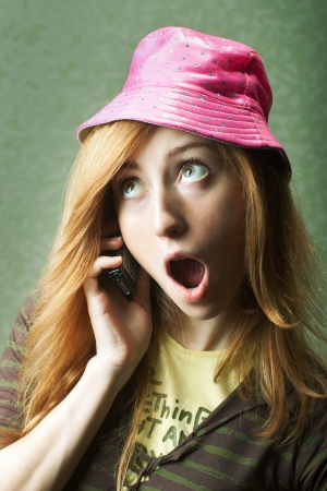 bimbo: Funny young woman in pink hat gossiping on mobile phone Stock Photo