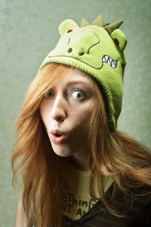 Surprised funny young woman with dragon hat photo