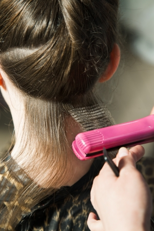 goffer: Closeup of crimping process using hair straightener with selective focus Stock Photo