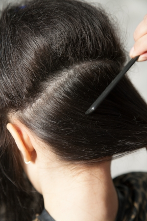 brune: Closeup of combing back side hair part with selective focus