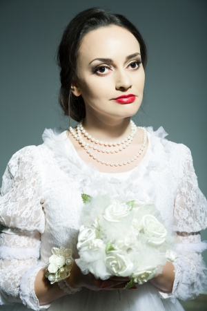 Studio portrait of bride in old-fashioned white dress holding flowers photo