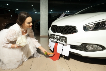 bride in white dress feeding a car with carrot photo