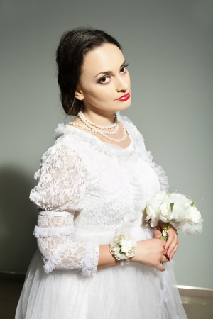 brune: Studio portrait of bride in old-fashioned white dress and flowers