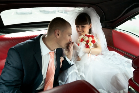 Groom kissing hand of bride with bouquet of flowers inside red car with selective focus photo