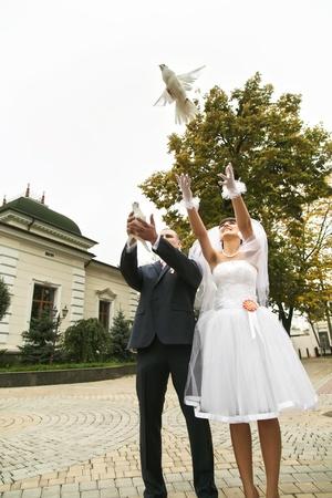 Bruid te laten witte duif vliegen met bruidegom buitenshuis Stockfoto